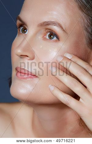 beautiful fourty year old woman with natural makeup and healthy skin texture on blue gray studio background touching her face