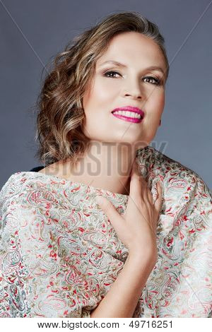 beautiful fourty year old woman with fashion makeup, curly hairstyle on grey blue studio background