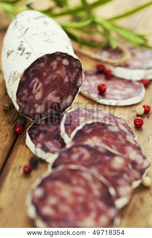 Close-up traditional sliced meat sausage salami on wooden board withrosemary