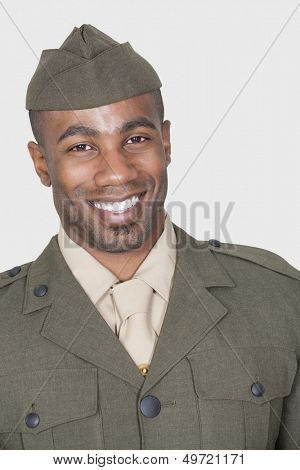 Portrait of a male African American US soldier smiling over gray background