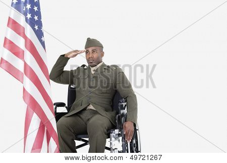 Young US soldier in wheelchair saluting American flag over gray background