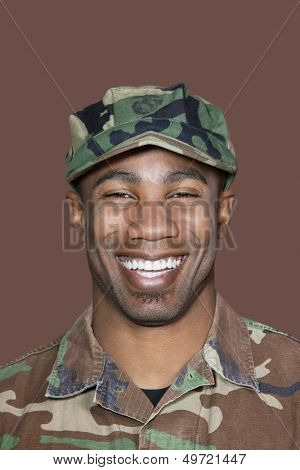 Portrait of a cheerful young African American US Marine Corps soldier over brown background