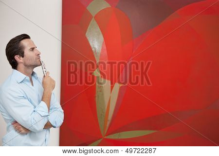 Thoughtful young man looking at painting in art gallery