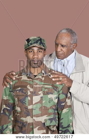 Portrait of African American male US Marine Corps soldier with father over brown background