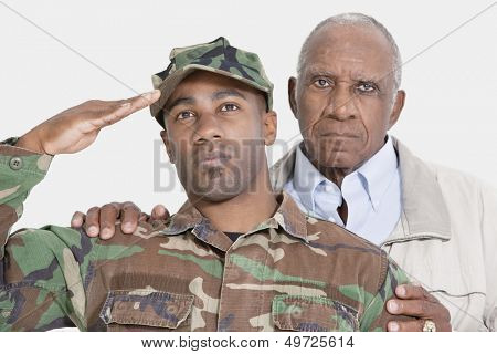 Portrait of US Marine Corps soldier with father saluting over gray background