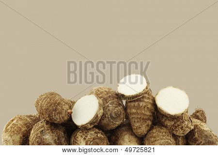 taro roots (colocasia) and some pieces on a brown background with copy space