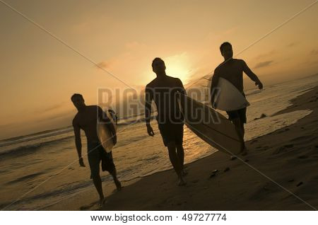 Full length of three surfers carrying surfboards out of surf at sunset