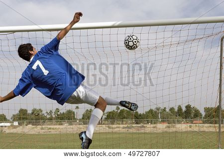 Rear view of young man scoring goal during soccer match