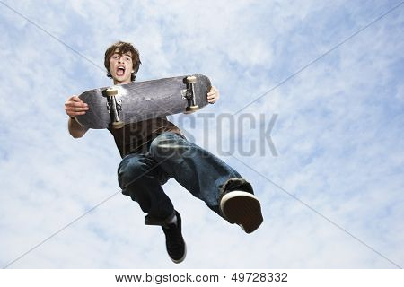 Low angle view of young man performing trick on skateboard
