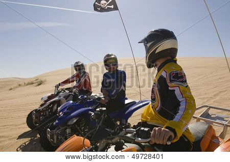 Three men on quadbikes in desert