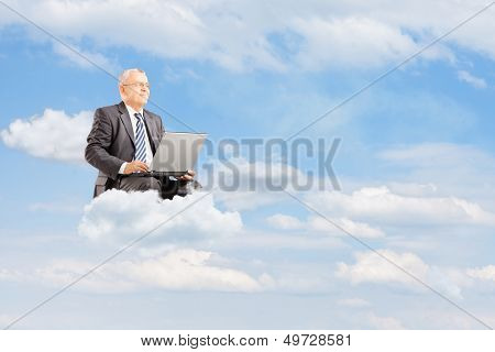 Mature businessman in suit flying on clouds with laptop against cloudy sky