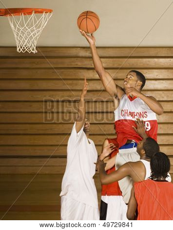 Young basketball player dunking basketball in hoop