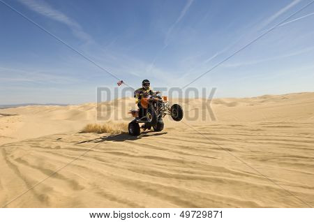 Young quad bike rider doing wheelie in desert
