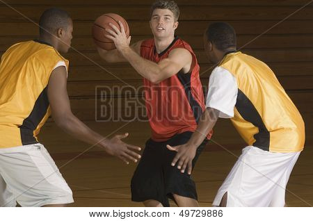 Young basketball player with ball being blocked by opponents
