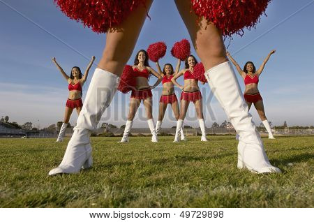Multiethnic cheerleaders with pom poms performing on field