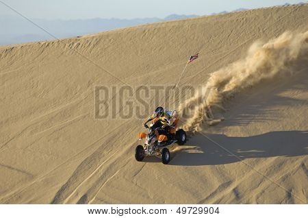 Young man riding ATV over sand dune in desert