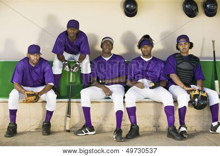 Tired baseball players sitting side by side in dugout