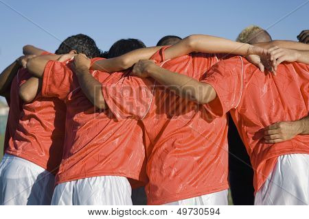 Rear view of young soccer players discussing strategy