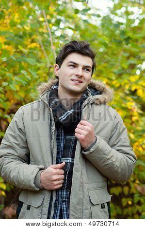 Young smiling man walking in park. Autumn autdoor.