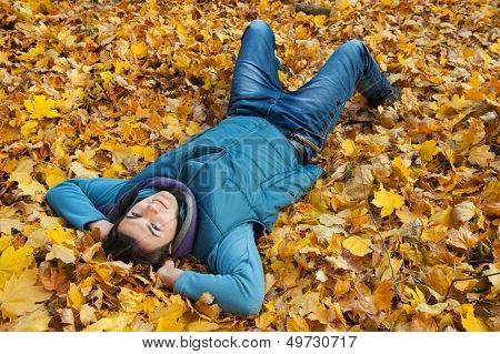 Young man laying in autumn park. Looking at camera.