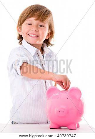 Boy saving money in a piggybank - isolated over white