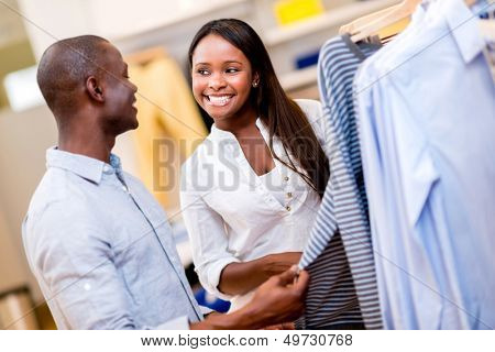 Happy couple shopping clothes at a retail store