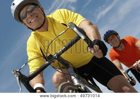 Low angle view of men riding bicycles against sky