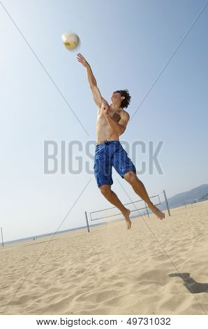 Low angle view of man playing volleyball on beach against clear sky