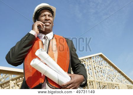 Low angle view of worker with blueprints using cell phone at construction site