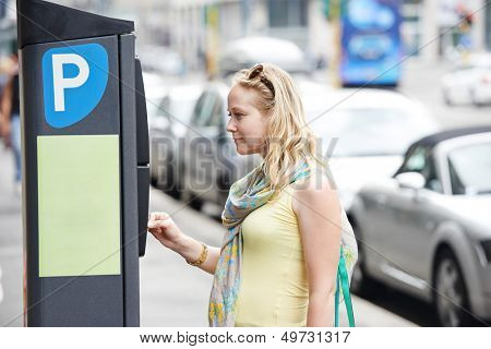 Young female woman paying for parking in the street