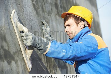 Young builder worker at facade plastering work during industrial building with putty knife float