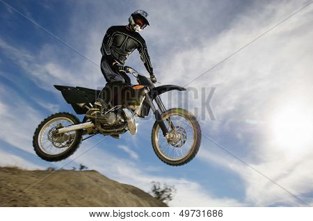 Low angle view of motocross racer in midair against cloudy sky