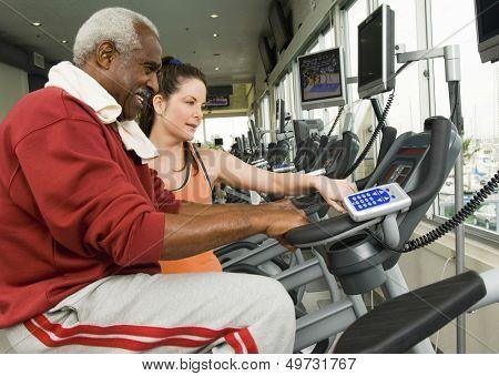 Female instructor assisting senior man on exercise bike at health club