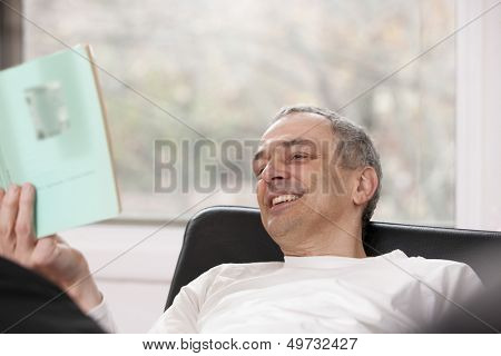 Relaxed smiling man reading a book at home