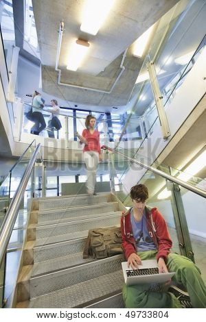University student using laptop on staircase with friends behind
