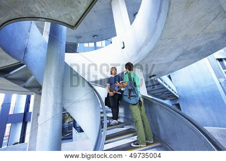 Low angle view of two male university students on staircase