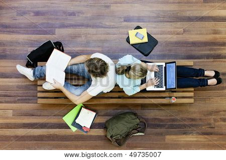 Top view of male and female university students studying