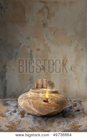 Ancient Middle Eastern oil lamp on clay surface
