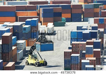 Heavy forklift handling container box during sorting in warehouse dock terminal of cargo sea port