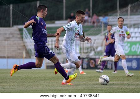 KAPOSVAR, HUNGARY - AUGUST 3: Benjamin Balazs (C) in action at a Hungarian National Championship soccer game - Kaposvar (white) vs Kecskemet (purple) on August 3, 2013 in Kaposvar, Hungary.