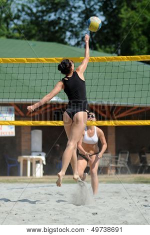 KAPOSVAR, HUNGARY - AUGUST 4: Zsofia Harmath (with ball) in action at a ROAK Viragfurdo Kupa beach volleyball competition, August 4, 2013 in Kaposvar, Hungary.