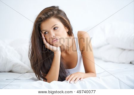 Brunette woman lying on white bed in bad mood