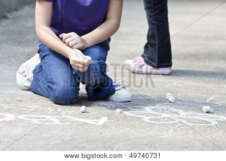 Back to school concept -Photo of girl writing with chalk on the schoolyard