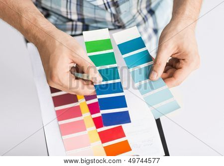 interior design and renovation concept - man with color samples for selection