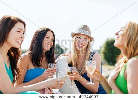 summer holidays and vacation - girls with champagne glasses on boat or yacht