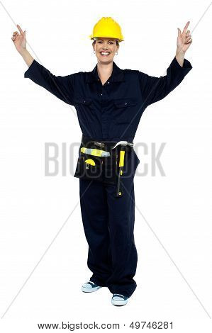 Smiling Lady Worker In Jumpsuit Raising Her Hands