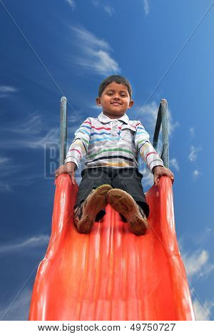 Beautiful Smiling(happy) Indian Boy(kid) On Slider In A Summer Day
