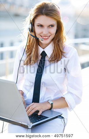 Busy call center operator works at laptop