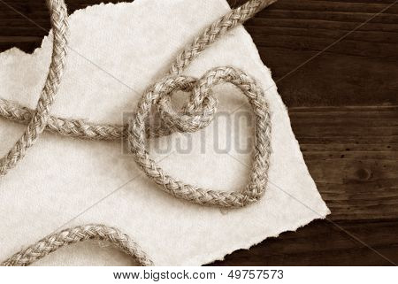 """Tying the knot' wedding invitation or save the date card in sepia tones. Rope knotted into a heart shape with hand torn parchment paper on rustic wood background. Macro with copy space."