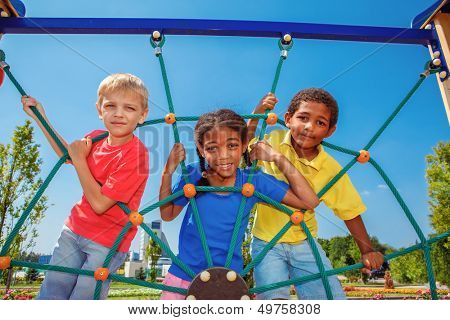 Friends climbing the net at the playground